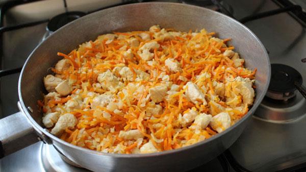 Кусочки курицы, морковка, лук на сковородке