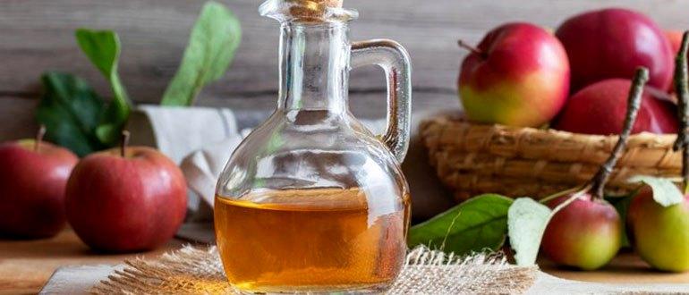 Яблочный уксус на фоне яблок