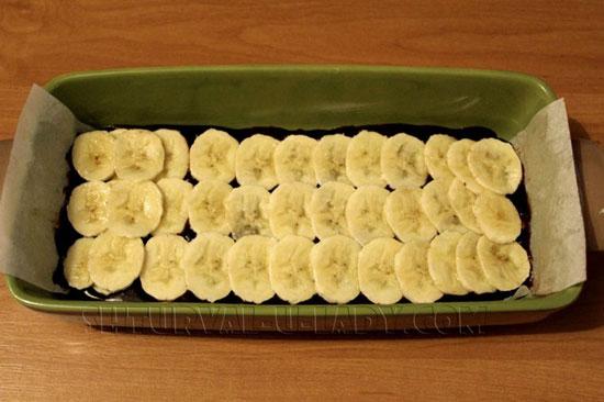 Выложенный слой банана поверх шоколадного теста брауни