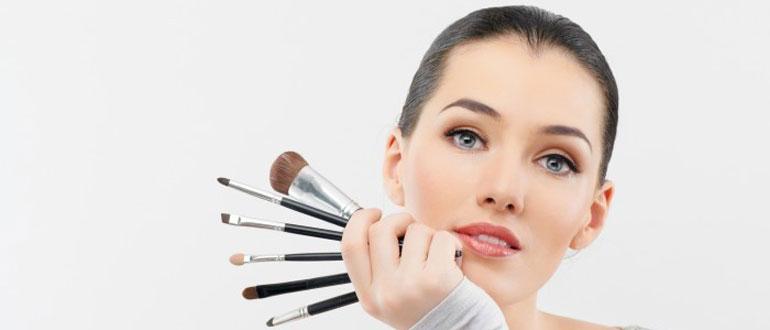 Разные кисти для макияжа в руке девушки