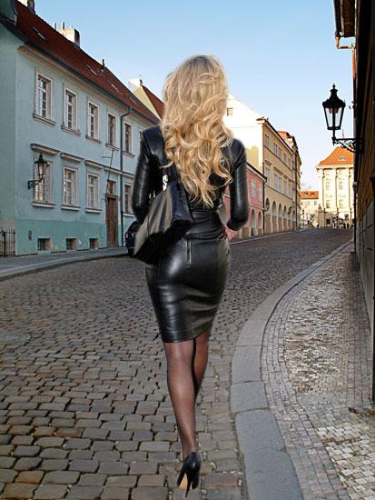 Девушка в черной кожаной юбке карандаш и пиджаке