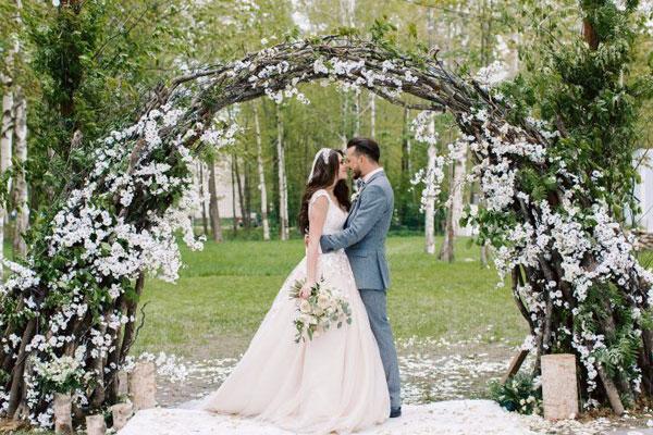Жених с невестой под свадебной аркой